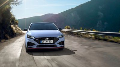 the new Hyundai i30 N from the front in Performance Blue colour driving on a mountain road