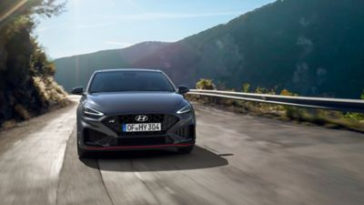 The new Hyundai i30 N driving in a hilly set in the colour Dark Knight Pearl.