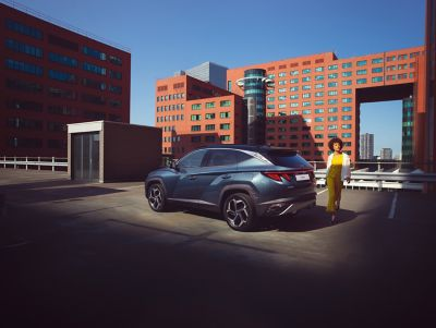 Een vrouw loopt voor haar geparkeerde Hyundai TUCSON langs, op een parkeerdak omringt door hoge gebouwen.