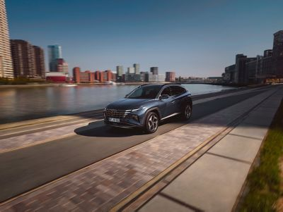 De nieuwe Hyundai TUCSON, rijdend langs het water in een stad.
