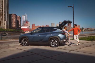 Twee mannen die met elkaar praten naast de nieuwe Hyundai Tucson. Eentje zit ontspannen op de rand van de kofferbak en de andere staat ernaast.