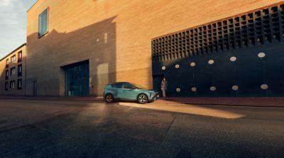 Een geparkeerde Hyundai BAYON, de nieuwe, compacte crossover-SUV, in de kleur Mangrove Green.