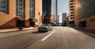 De Hyundai BAYON, de nieuwe, compacte crossover-SUV, gezien van de voorzijde, rijdend in een stad.