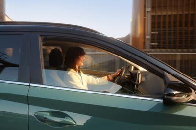 Vrouw bestuurt de Hyundai BAYON, de nieuwe, compacte crossover-SUV, met een panoramisch zonnedak.