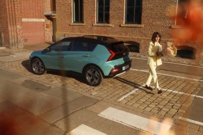 Woman in yellow walking away from the parked all-new Hyundai BAYON compact crossover SUV.