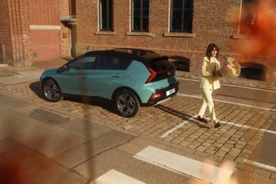 In geel geklede vrouw loopt weg van een geparkeerde Hyundai BAYON, de nieuwe, compacte crossover-SUV.