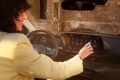 """Donna che utilizza il touchscreen da 10,25"""" nel nuovissimo SUV crossover compatto Hyundai BAYON."""