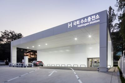 A hydrogen filling station pictured with a Hyundai vehicle driving into it.