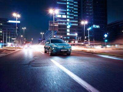 Kona Electric kjørende på en vei om natten. Foto.