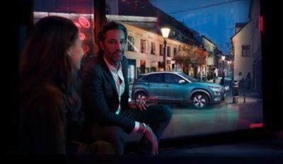 Mężczyzna siedzi przy oknie, na ulicy stoi zaparkowany Hyundai KONA Electric.