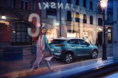 Dame titter inn av et vindu før hun passerer en Kona Electric parkert på gaten. Foto.