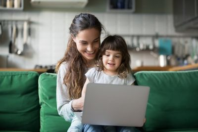 Mother and daughter sitting on a green couch, laptop in front of them.