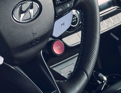 Detail of the red N Grin Shift button on the steering wheel of the Hyundai KONA N.