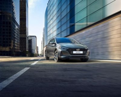 The all-new Hyundai i20 parked next to large buildings in an otherwise empty street