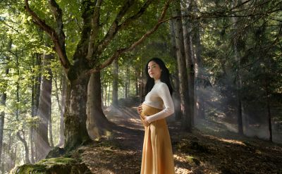 A pregnant woman picture in a forest holding her baby bump.