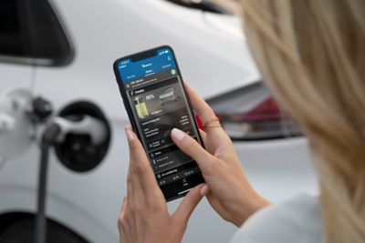 Picture of a woman checking the charging status of her Hyundai  Ioniq Hybrid on an app