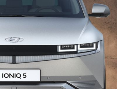 The Hyundai IONIQ 5 electric midsize CUV from the front showing its distinctive LED headlamps.