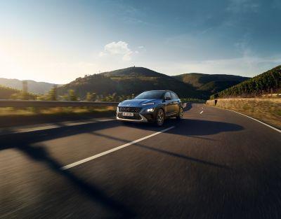 Nowy Hyundai KONA w kolorze Surfy Blue jedzie malowniczą drogą – ujęcie z przodu.