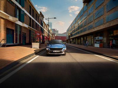 Nowy Hyundai KONA w kolorze Surfy Blue jedzie ruchliwą ulicą – ujęcie z przodu.