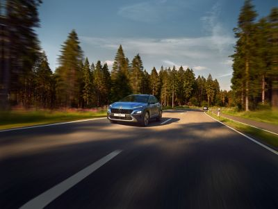The new Hyundai Kona from the front in Surfy Blue driving down a forest road.