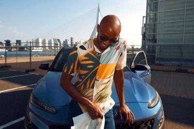 Mężczyzna oparty o maskę nowego Hyundaia Kona Hybrid w kolorze Surfy Blue.
