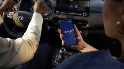 Passager utilisant Bluelink à l'intérieur du nouveau SUV urbain Hyundai KONA Hybrid.