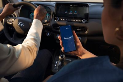 Immagine di una ragazza seduta all'interno di una vettura Hyundai con in mano un telefono con una schermata dell'app Bluelink