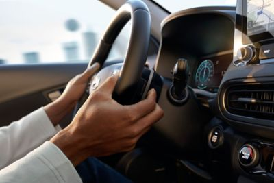 Immagine ravvicinata dei comandi al volante del SUV compatto Nuova Hyundai KONA Hybrid.