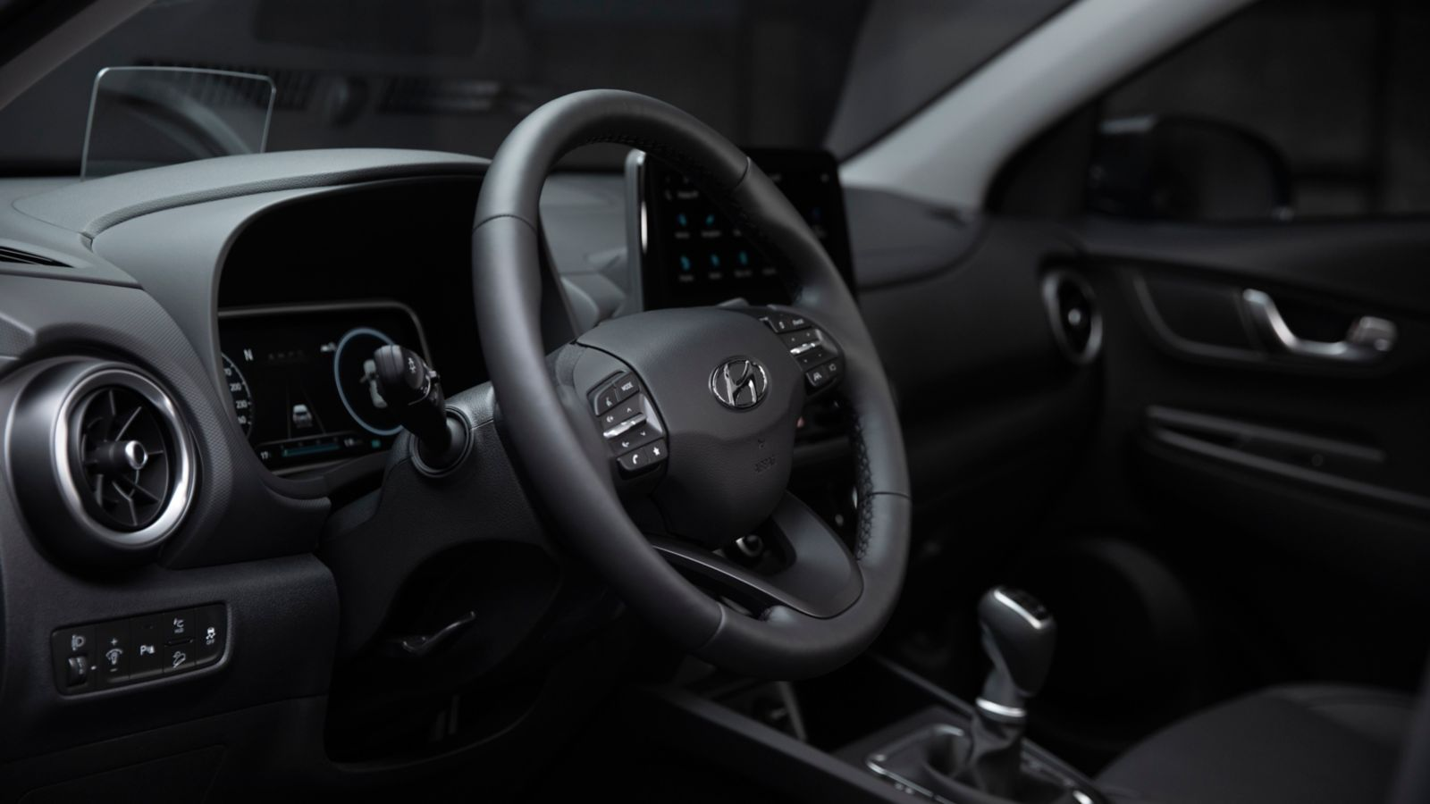 Interior view in the new Hyundai Kona Hybrid compact SUV showing the co-driver using Bluelink®.