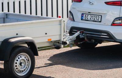 Elbilen KONA Electric med hengerfeste og tilhenger med hageavfall. Foto.
