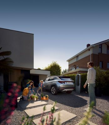 Family next of the all-new Hyundai TUCSON Plug-in Hybrid N Line in a housing area.
