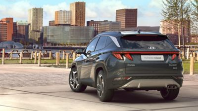 The all-new Hyundai Tucson compact SUV pictured from the rear parked near a waterfront skyline.