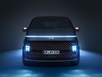 The all-new Hyundai STARIA Premium multi-purpose vehicle from the front with the lights on.