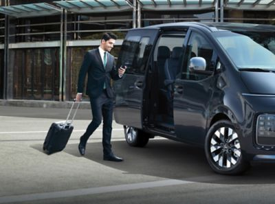 A business man checking his phone, going towards the all-new Hyundai Staria Premium.