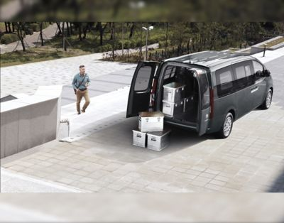 The all-new STARIA Van pictured with open twin doors and boxes as cargo.