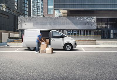 The all-new STARIA Van parked at a curb, delivery guy unpacking from the side door.