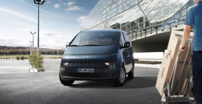 The all-new Hyundai STARIA Van in a parking lot from the front.