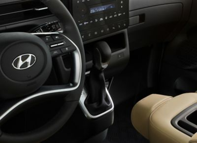 A detailed view of the all-new STARIA's driving wheel and stylish gearshift in the centre console.