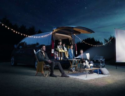 Family having a movie night while camping with the all-new Hyundai STARIA.