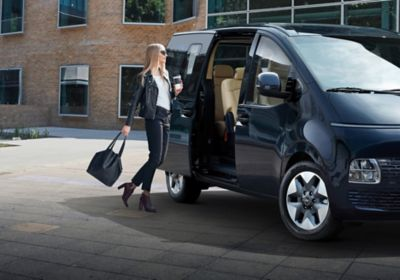 A woman holding a cup of coffee getting into the all-new Hyundai STARIA.