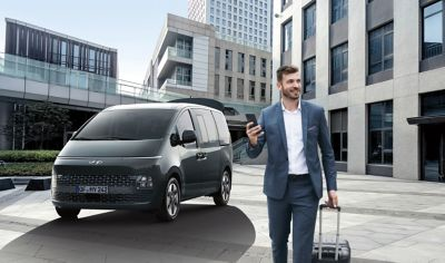 Business man walking away from the all-new Hyundai STARIA with smart power tailgate.