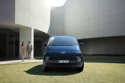 The all-new Hyundai STARIA from the front parked in a public yard.