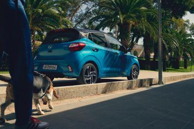 Hyundai i10 driekwart achter naast persoon met hond.