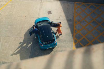 Vista superior de una pareja entrando en su Hyundai i10 de color azul.