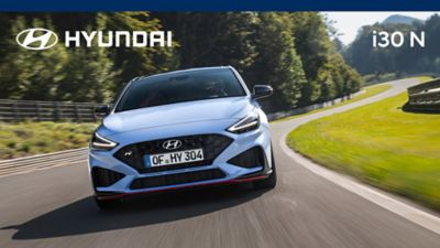 The new Hyundai i30 N from the front in Performance Blue colour driving down a race track.