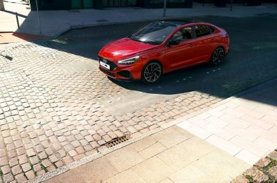 A new Hyundai i30 Fastback N Line parked on a cobblestone street.