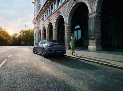 Kobieta idąca w stronę nowego Hyundaia i30 Fastback zaparkowanego na ulicy