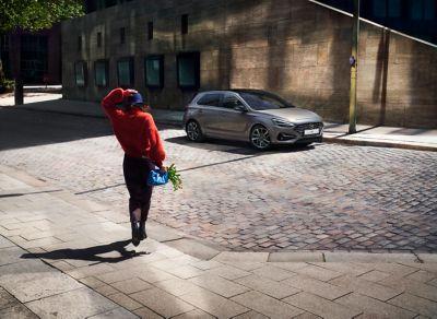 Vrouw wandelt richting de nieuwe i30 Hatchback die geparkeerd is in een straat.