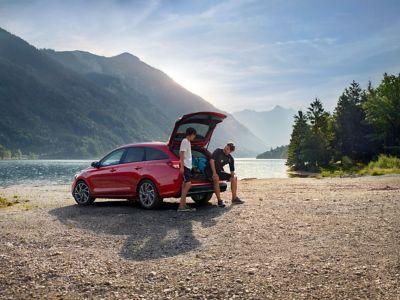 Mężczyzna z synem stoją przy samochodzie Hyundai z otwartym bagażnikiem.