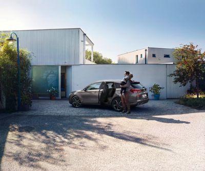 Man met kind op zijn arm, voor zijn nieuwe Hyundai i30 Wagon.